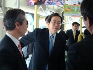 路面電車に乗り、利用実態を聞く斉藤鉄夫(中)